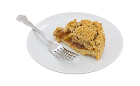 side plate: Side view of a slice of Dutch apple pie on a plate with a fork isolated on a white background.