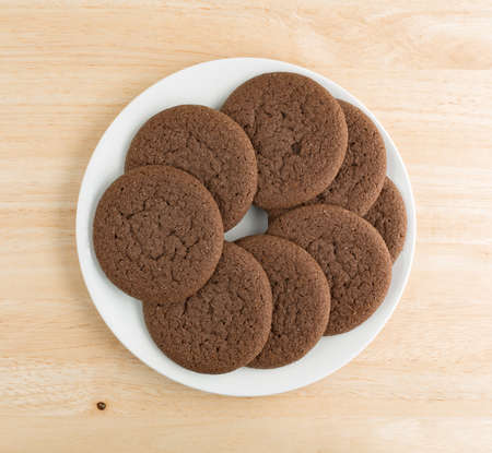 atop: Top view of several Dutch cocoa cookies on a white plate atop a wood table top.