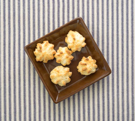 free dish: Top view of a serving of sugar free coconut macaroons in a small dish atop a blue striped tablecloth.