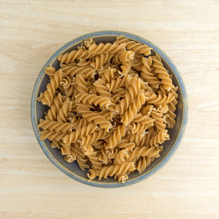 stoneware: Top view of an old stoneware bowl filled with fusilli whole wheat organic pasta on a wood table top. Stock Photo