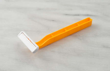 counter top: Side view of a generic disposable shaving razor on a marble counter top.