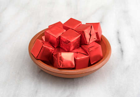 Several beef flavored bouillon cubes in red tinfoil wrappers filling a small dish atop a gray marble cutting board.