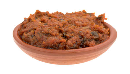 sun dried: A small bowl filled with tomato pesto sauce with sun dried tomatoes and pine nuts isolated on a white background.