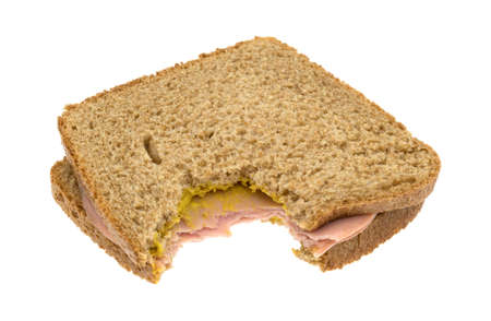 Side view of a mortadella sandwich on whole wheat bread with mustard that has been bitten once isolated on a white background.