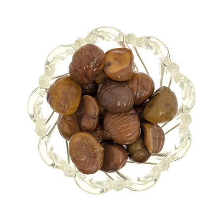 Top view of a glass bowl filled with organic whole shelled roasted chestnuts isolated on a white background.