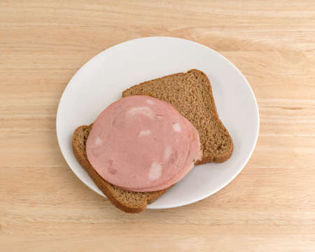 A mortadella sandwich in whole wheat bread open faced upon a white plate atop a wood table top.