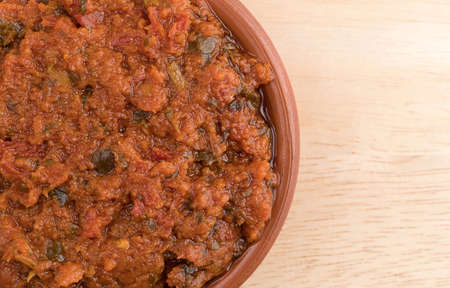 sun dried: Top close view of a small bowl filled with tomato pesto sauce with sun dried tomatoes and pine nuts on a wood table. Stock Photo