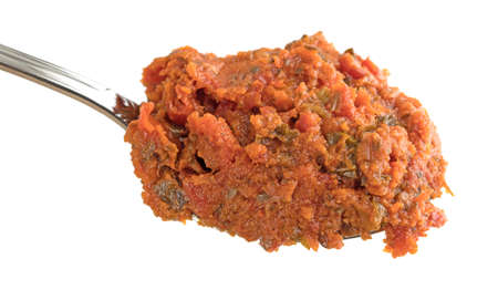 sun dried: A small portion of tomato pesto sauce with sun dried tomatoes and pine nuts on a spoon against a white background.