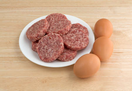 counter top: A white plate with sausage patties and eggs to the side atop a wood counter top.