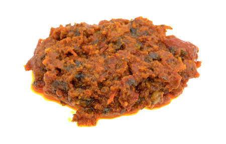 sun dried: A small portion of tomato pesto sauce with sun dried tomatoes and pine nuts isolated on a white background.