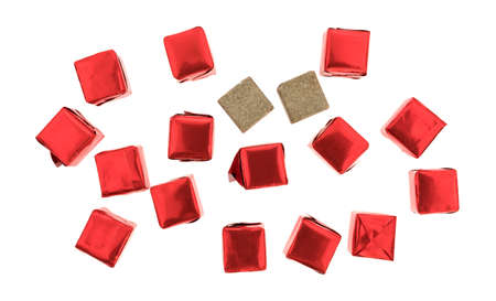 Top view of several beef flavored bouillon cubes in red tinfoil wrappers plus two unwrapped ready to use isolated on a white background.
