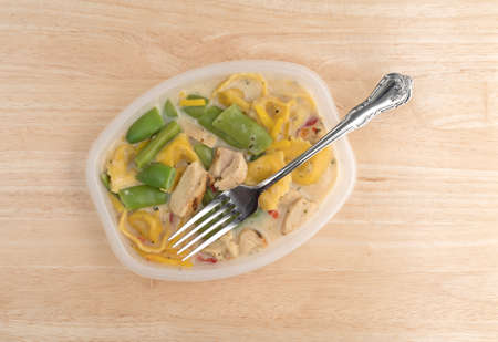 vegetable tray: Top view of a chicken with tortellini and vegetable TV dinner in a plastic tray with a fork in the food atop a wood table. Stock Photo
