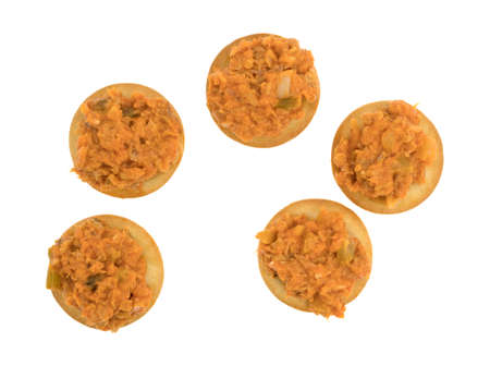 chicken salad: Top view of several spicy chicken salad on a butter crackers isolated on a white background. Stock Photo