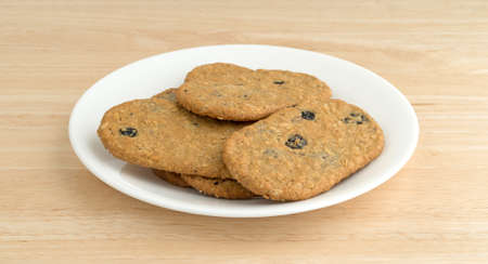 side plate: Side view of blueberry wafer cookies on a white plate atop a wood table top.