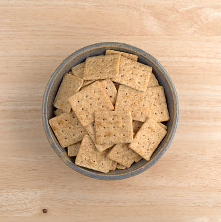 stoneware: Top view of an old stoneware bowl filled with organic whole wheat crackers on a wood table.
