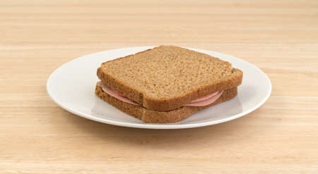 A mortadella sandwich in whole wheat bread upon a white plate atop a wood table top.
