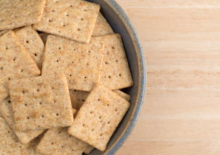 stoneware: Top close view of an old stoneware bowl filled with organic whole wheat crackers on a wood table.