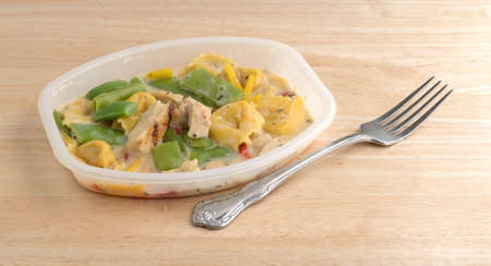 Side view of a chicken with tortellini and vegetable TV dinner in a plastic tray with a fork atop a wood table.