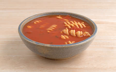 stoneware: Rotini tomato soup in an old stoneware bowl on a wood table top.