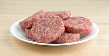 A white plate with sausage patties atop a wood counter top. Banco de Imagens