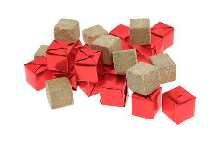 Several beef flavored bouillon cubes in red tinfoil wrappers plus unwrapped ready to use isolated on a white background.