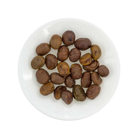 shelled: Top view of a plate with organic whole shelled roasted chestnuts isolated on a white background. Stock Photo