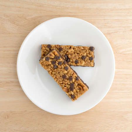 atop: Top view of two chocolate chip with peanuts protein bars on a plate atop a wood table top.