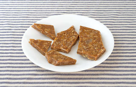 brittle: Several pieces of ginger brittle on a white plate atop a blue striped tablecloth. Stock Photo