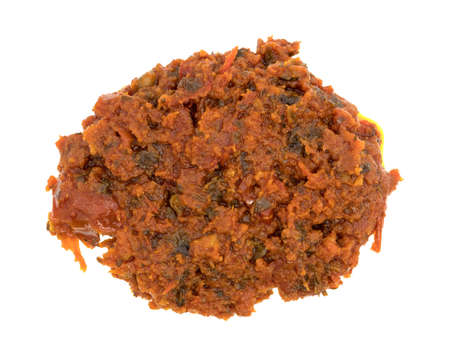 sun dried: Top view of a small portion of tomato pesto sauce with sun dried tomatoes and pine nuts isolated on a white background. Stock Photo