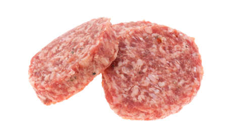 Fresh sausage patties isolated on a white background.