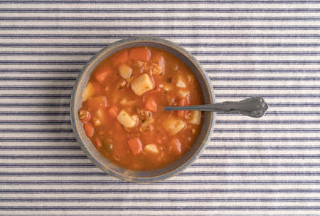 stoneware: Top view of a serving of Manhattan style clam chowder in an old stoneware bowl with a spoon inserted into the food on striped tablecloth.
