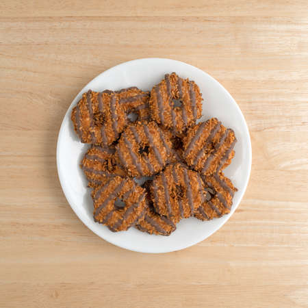 Top view of several fudge with coconut and caramel cookies on a white plate atop a wood table. Stock Photo