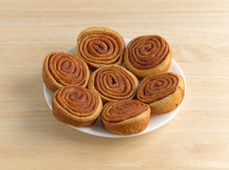 Several pecan sweet rolls on a white plate atop a wood table.