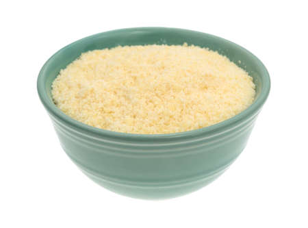 grated parmesan cheese: A green bowl filled with freshly grated parmesan cheese on a white background.