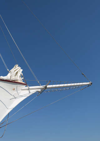View of a bowsprit of a large wooden sailboat against blue sky with canvas sails.