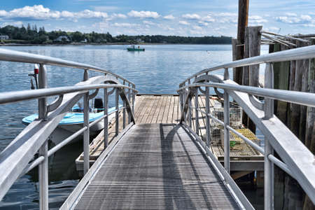 A floating dock with a lobster boat in the distance at Searsport, Maine. Stock Photo