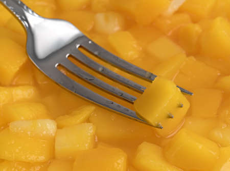 A diced mango on the tines of a fork with more fruit in light syrup.
