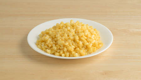 Shoepeg white corn with a butter sauce on a white plate atop a wood table.