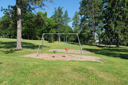 swing set: A toddlers swing set that is empty in a park setting.