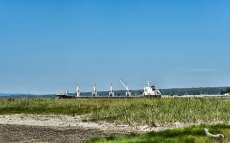 sears: A cargo ship at a commercial port in the distance from Sears Island at Searsport, Maine in the summertime.