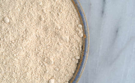 Top close view of a bowl filled with quinoa flour on a gray marble cutting board. Reklamní fotografie