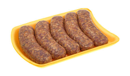 Spicy bratwurst links on a yellow foam butcher tray atop a white background.