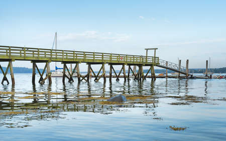 A long pier with moored sailboats in the distance.