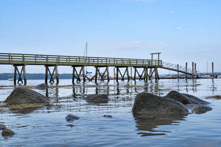 dinghies: A long pier with moored sailboats in the distance with rocks in the foreground at low tide.