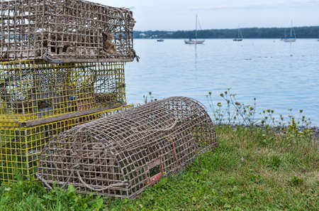 traps: Several old lobster traps on shore with sailboats moored in the distance on the coast of Maine in the summertime. Stock Photo