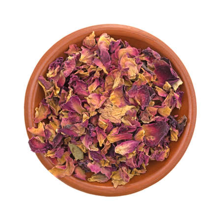 Top view of a bowl of dried red rosebuds and petals that have been crushed isolated on a white background. Banco de Imagens