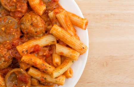 marinara sauce: Top close view of a serving of rigatoni pasta with sausage and meatballs in a marinara sauce on a plate atop a wood table.