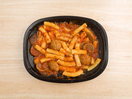 marinara sauce: Top view of a TV dinner of rigatoni pasta with sausage and meatballs in a marinara sauce on a wood table.
