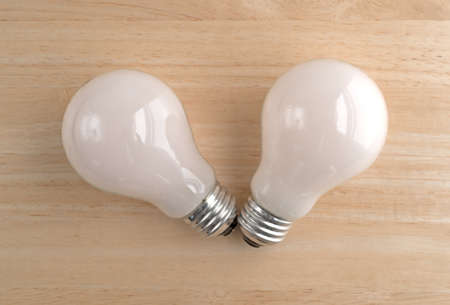 Top view of two soft white energy saving light bulbs on a wood table.