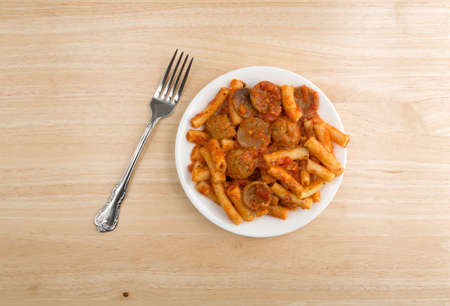 marinara sauce: Top view of a serving of rigatoni pasta with sausage and meatballs in a marinara sauce on a plate with a fork to the side atop a wood table.